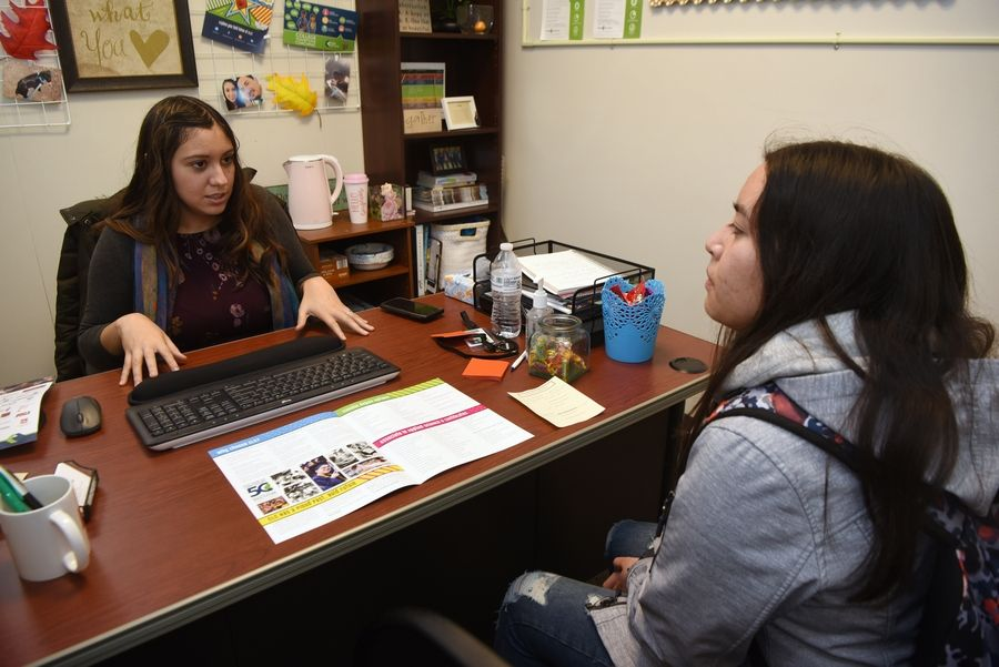 College of Lake County College Transitions Coach Eileen Rancharan meets with senior Jessica Zamudio at Mundelein High School. Embedding Rancharan at the high school is an experiment CLC is testing this year to build relationships with students and families and help them through the financial aid and college application processes.