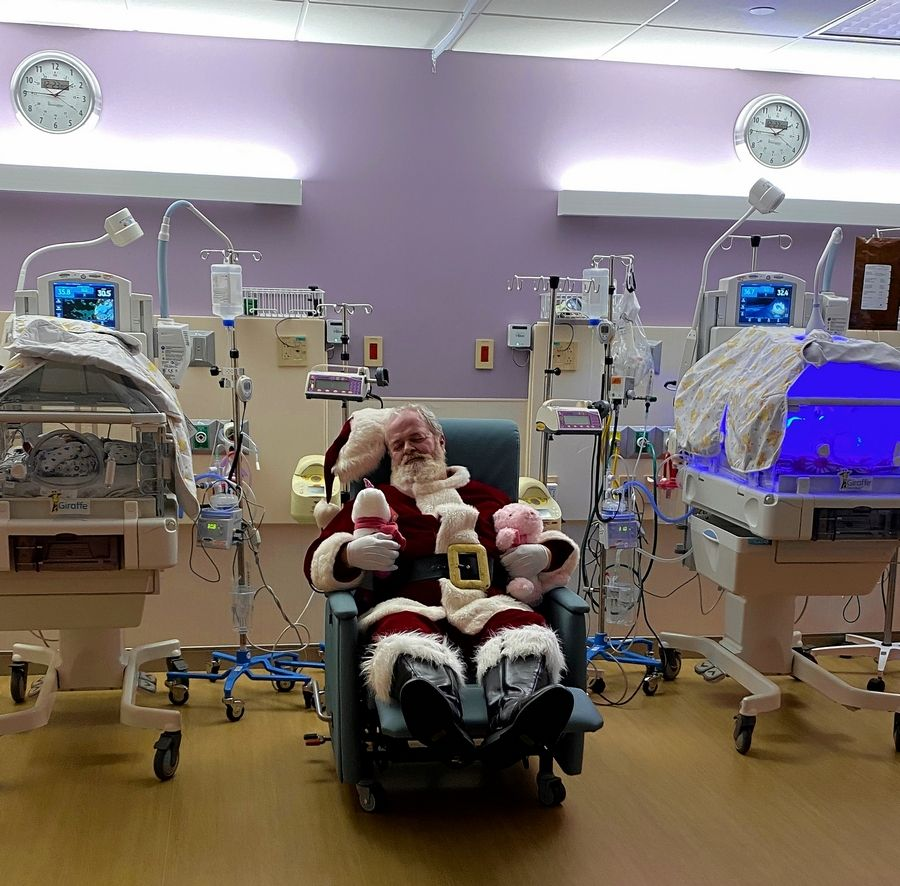 Santa, played by Timothy Connell of Lisle, takes a quick rest between two napping babies in the Northwestern Medicine Central DuPage Hospital neonatal intensive care unit.