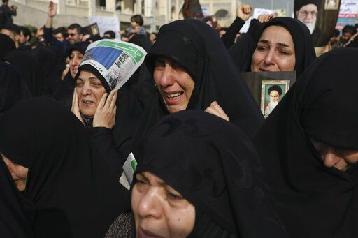 "Women weep while mourning during a demonstration over the U.S. airstrike in Iraq that killed Iranian Revolutionary Guard Gen. Qassem Soleimani, in Tehran, Iran, Jan. 3, 2020. Iran has vowed ""harsh retaliation"" for the U.S. airstrike near Baghdad's airport that killed Tehran's top general and the architect of its interventions across the Middle East, as tensions soared in the wake of the targeted killing."