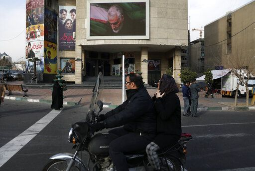 "People make their way on the street while a screen on the wall of a cinema shows a portrait of Iranian Revolutionary Guard Gen. Qassem Soleimani, who was killed in the U.S. airstrike in Iraq that killed, in Tehran, Iran, Jan. 3, 2020.  Iran has vowed ""harsh retaliation"" for the U.S. airstrike near Baghdad's airport that killed Tehran's top general and the architect of its interventions across the Middle East, as tensions soared in the wake of the targeted killing."