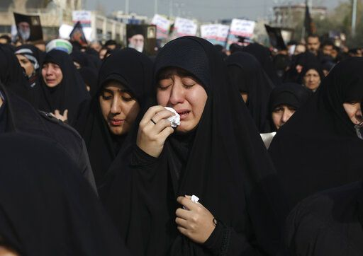 "A women weeps while mourning during a demonstration over the U.S. airstrike in Iraq that killed Iranian Revolutionary Guard Gen. Qassem Soleimani, in Tehran, Iran, Jan. 3, 2020. Iran has vowed ""harsh retaliation"" for the U.S. airstrike near Baghdad's airport that killed Tehran's top general and the architect of its interventions across the Middle East, as tensions soared in the wake of the targeted killing."