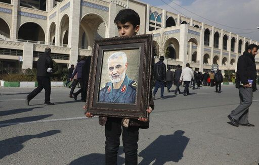 "A boy carries a portrait of Iranian Revolutionary Guard Gen. Qassem Soleimani, who was killed in the U.S. airstrike in Iraq, prior to the Friday prayers in Tehran, Iran, Friday Jan. 3, 2020. Iran has vowed ""harsh retaliation"" for the U.S. airstrike near Baghdad's airport that killed Tehran's top general and the architect of its interventions across the Middle East, as tensions soared in the wake of the targeted killing."