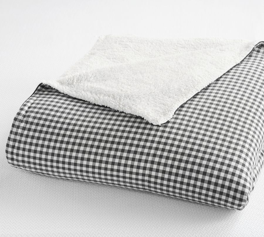 Pottery Barn's Gingham Sherpa blanket has a smart black and white checked pattern on one side, and soft fluffy Sherpa fabric on the other. It would blend well with tailored bedroom accessories, feminine florals, and a wide range of color palettes.