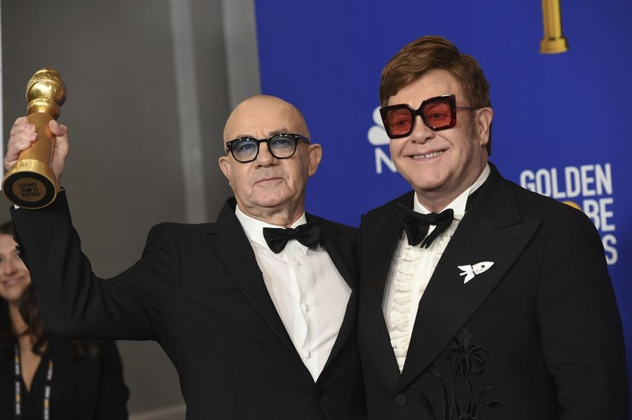 "Elton John, right, and Bernie Taupin pose in the press room with the award for best original score in a motion picture for ""I'm Gonna Love Me Again"" from ""Rocketman"" at the 77th annual Golden Globe Awards at the Beverly Hilton Hotel on Sunday, Jan. 5, 2020, in Beverly Hills, Calif."