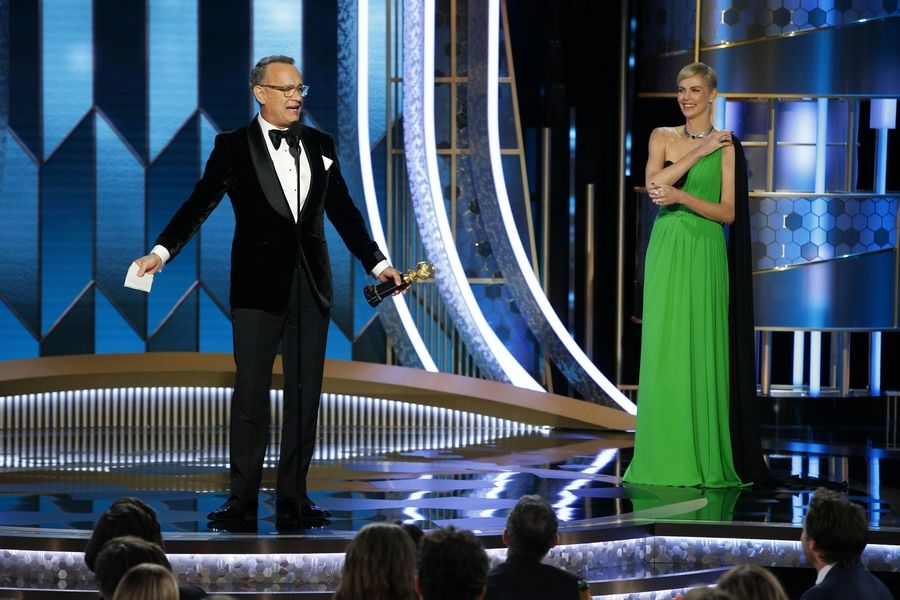 This image released by NBC shows Tom Hanks accepting the Cecil B. DeMille Award as presenter Charlize Theron looks on at right at the 77th Annual Golden Globe Awards at the Beverly Hilton Hotel in Beverly Hills, Calif., on Sunday, Jan. 5, 2020.