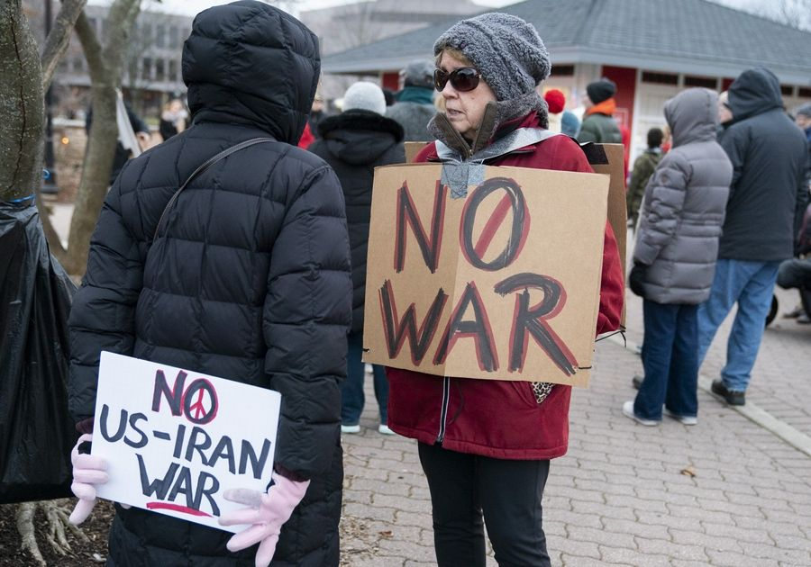 Karen Peck, left, of Naperville, and Jacque Cooley, of Wheaton, talk before an anti war rally to protest the latest tensions with Iran on Sunday along the Naperville Riverwalk in Naperville.