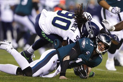 Seattle Seahawks' Jadeveon Clowney (90) hits Philadelphia Eagles' Carson Wentz (11) during the first half of an NFL wild-card playoff football game, Sunday, Jan. 5, 2020, in Philadelphia.