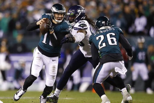 Philadelphia Eagles' Josh McCown (18) tries to get past Seattle Seahawks' Jadeveon Clowney (90) as Miles Sanders (26) tries to defend during the first half of an NFL wild-card playoff football game, Sunday, Jan. 5, 2020, in Philadelphia.