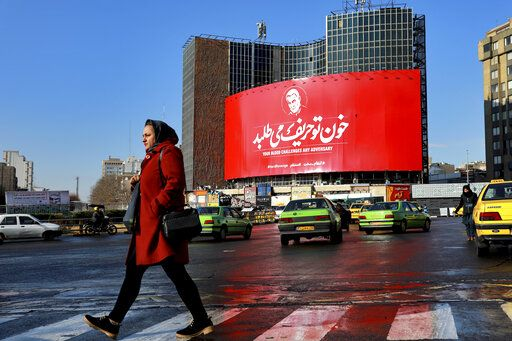 A woman crosses a street in front of a billboard showing a portrait of Iranian Revolutionary Guard Gen. Qassem Soleimani, who was killed in a U.S. airstrike early Friday in Iraq, in Tehran, Iran, Sunday, Jan. 5, 2020. The body of Gen. Soleimani arrived Sunday in Iran to throngs of mourners.  President Donald Trump issued a stark warning to Iran on Saturday, threatening to hit dozens of targets in the Islamic Republic 'œvery fast and very hard'� if it retaliates for the targeted killing of the head of the Iran's elite Quds Force.