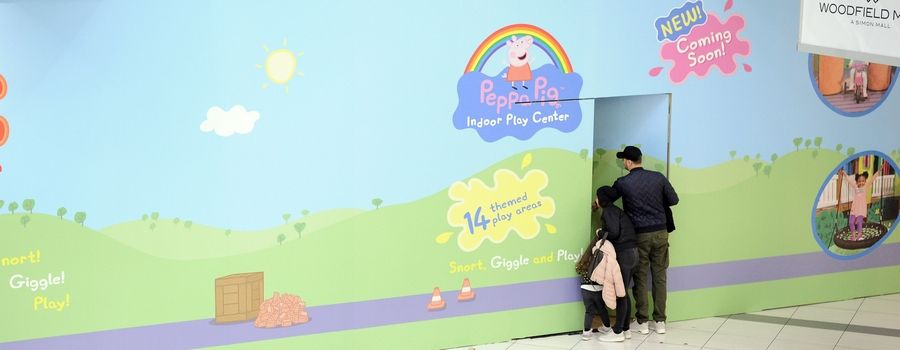 A family walking by the former Rainforest Cafe site in Woodfield Mall takes a peek inside to see the new Peppa Pig World of Play that will replace the closed restaurant the lower level of the Schaumburg shopping center.