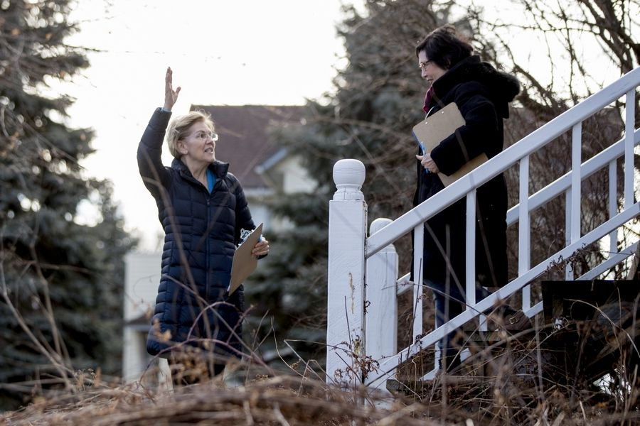 Democratic presidential candidate Sen. Elizabeth Warren, D-Mass., left, accompanied by Jackson County Democratic Party chair Donna Duvall, right, waves to a couple who sign up with her as she knocks on doors to speak to undecided caucus goers, Sunday, Jan. 5, 2020, in Maquoketa, Iowa.