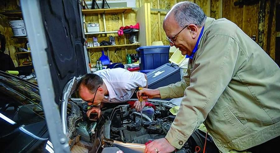 Frank Hauser, right, works with mechanic Kevin Lang to give donated cars new lives at the Good News Garage at Trinity Lutheran Church in Des Plaines.