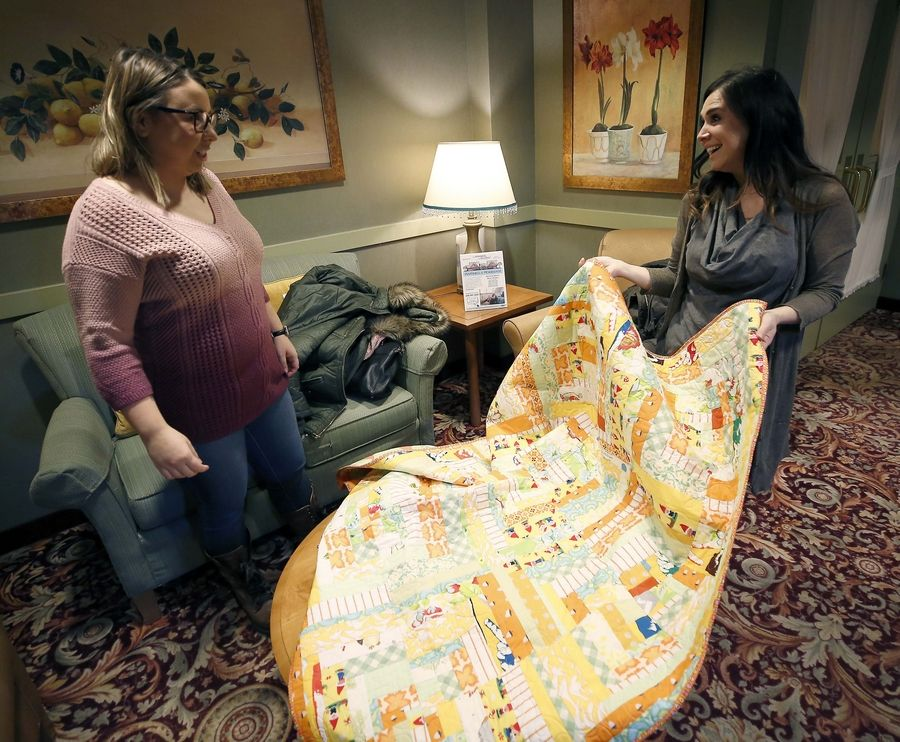 Event coordinator Amy Paauwe and Co-owner Gayle Schliemann of BERNINA of Naperville deliver quilts Wednesday to patients at Alden of Waterford rehabilitation center in Aurora after making them during the store's grand opening sew-a-thon in November.