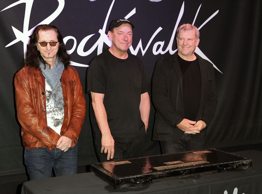Members of the band Rush, from left, Geddy Lee, Neil Peart, and Alex Lifeson at the RockWalk induction of Rush at Guitar Center in Los Angeles. Peart died Tuesday in Santa Monica, California, at age 67.