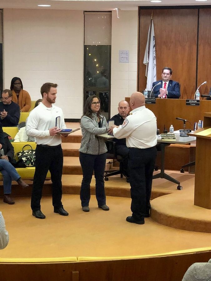 Carpentersville Fire Chief John-Paul Schilling presents Dundee-Crown High School athletic trainer Brenna Tschida and coach Connor Loehrke with lifesaving awards at a recent village board meeting.