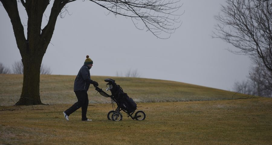 A golfer braves strong winds and light snow during the Arlington Heights Park District's annual Chilly Open at Arlington Lakes Golf Club Saturday.