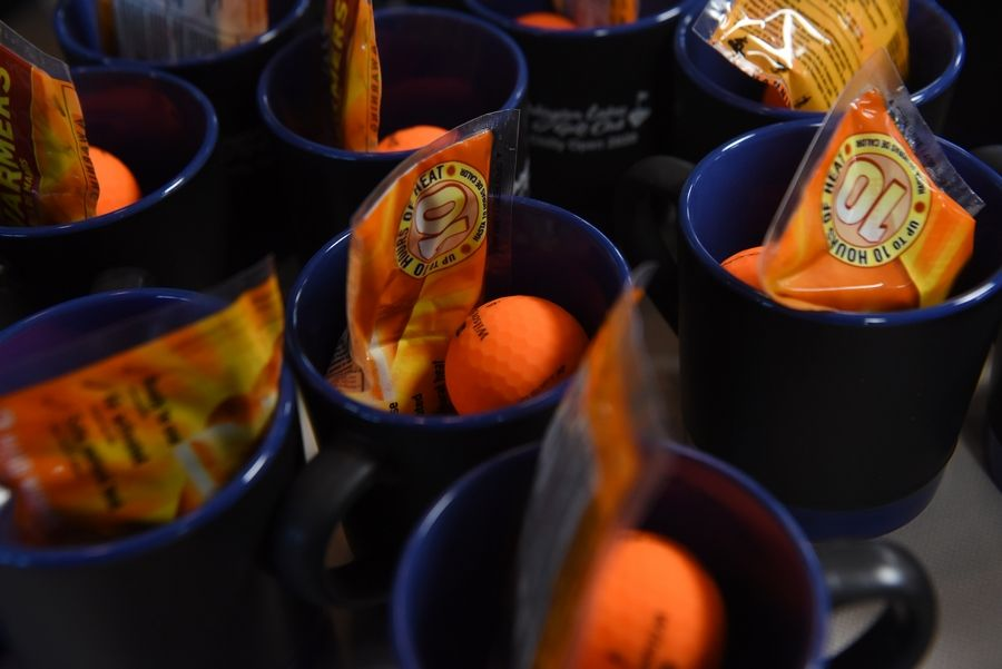 Mugs include an orange golf ball and handwarmers at the registration table of the Arlington Heights Park District's annual Chilly Open at Arlington Lakes Golf Club Saturday.