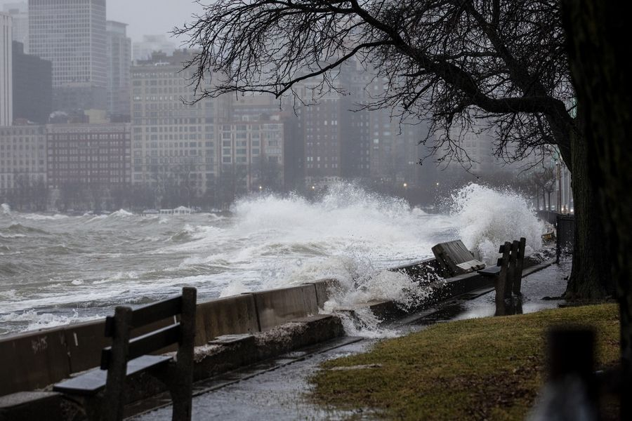 High waves from Lake Michigan hit the lakefront trail near North Avenue as a winter storm moves through the Chicago area Saturday. Freezing rain left roads and trees glazed with ice Saturday across parts of northern Illinois and cut power to about 5,000 homes and businesses.