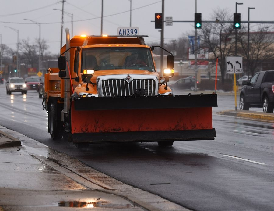 With the threat of a winter storm looming, a plow truck passes Arlington Heights Road while traveling west on Golf Road in Arlington Heights Saturday.