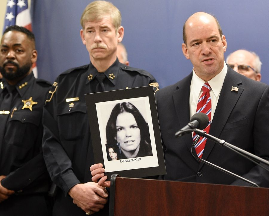 State's Attorney Robert Berlin and Sheriff James Mendrick display a photo of Deborah McCall, the victim of an unsolved murder they suspect also was committed by Bruce Lindahl.