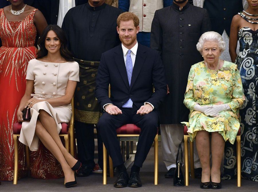 "FILE - In this Tuesday, June 26, 2018 file photo, Britain's Queen Elizabeth, Prince Harry and Meghan, Duchess of Sussex pose for a group photo at the Queen's Young Leaders Awards Ceremony at Buckingham Palace in London. As part of a surprise announcement distancing themselves from the British royal family, Prince Harry and his wife Meghan declared they will ""work to become financially independent"" _ a move that has not been clearly spelled out and could be fraught with obstacles.(John Stillwell/Pool Photo via AP, File)"