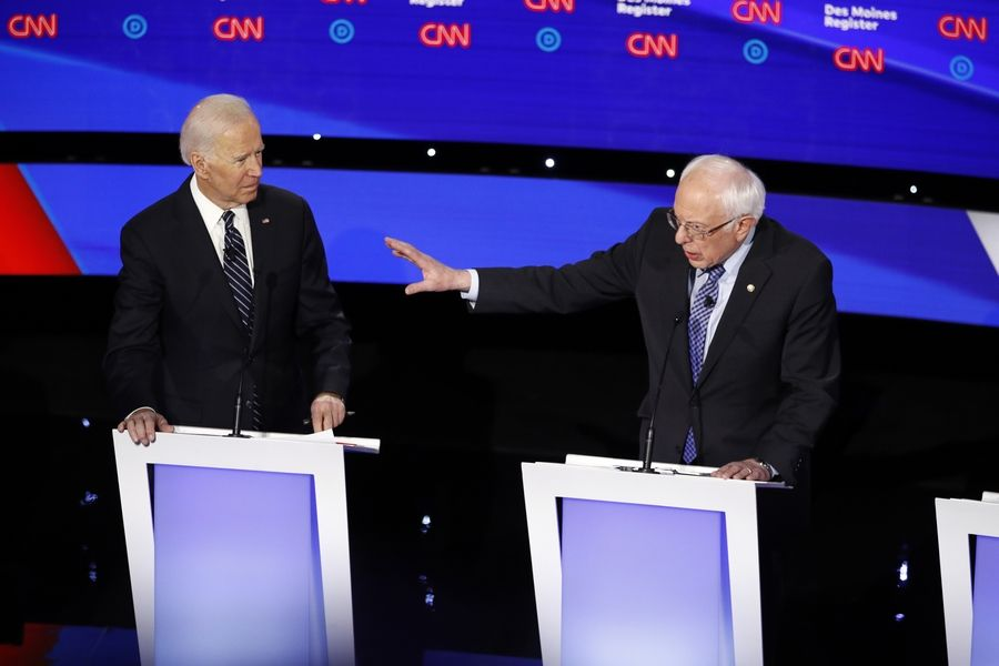 Democratic presidential candidate former Vice President Joe Biden, left, watches as Sen. Bernie Sanders, I-Vt., answers a question Tuesday, Jan. 14, 2020, during a Democratic presidential primary debate hosted by CNN and the Des Moines Register in Des Moines, Iowa.