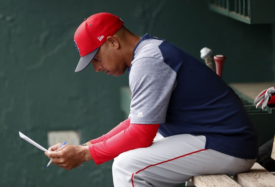 FILE - In this March 20, 2019, file photo, Boston Red Sox manager Alex Cora looks over the lineup before the team's spring training baseball game against the Baltimore Orioles in Sarasota, Fla. Cora was fired by the Red Sox on Tuesday, Jan. 14, 2020, a day after baseball Commissioner Rob Manfred implicated him in the sport's sign-stealing scandal.