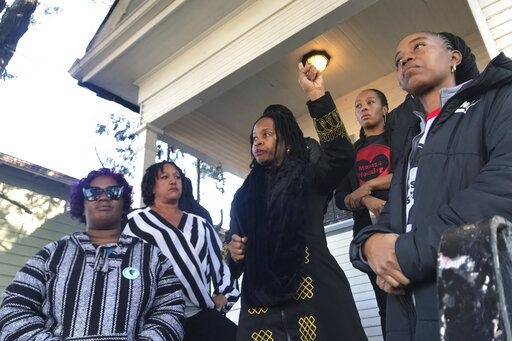 FILE - In this Dec. 30, 2019, file photo, Sharena Thomas, left, Carroll Fife, center, Dominique Walker, second from right, and Tolani KIng, right, stand outside a vacant home they took over on Magnolia Street in West Oakland, Calif. Homeless women ordered by a judge last week to leave a vacant house they occupied illegally in Oakland for two months have been evicted by sheriff's deputies. They removed two women and a male supporter Tuesday, Jan. 14, 2020, from the home before dawn in a case highlighting California's severe housing shortage and growing homeless population. (Kate Wolffe/KQED via AP, File)
