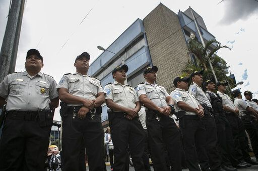 Police stand guard in front of the Central American Parliament, behind, where outgoing President Jimmy Morales will arrive to join the parliament as a lawmaker, in Guatemala City, Tuesday, Jan. 14, 2020. Guatemala will inaugurate on Tuesday a new president as Morales exits amid swirling corruption accusations.