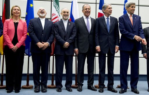 FILE - In this July 14, 2015 file photo, from left to right: European Union High Representative Federica Mogherini, Iranian Foreign Minister Mohammad Javad Zarif, Head of the Iranian Atomic Energy Organization Ali Akbar Salehi, Russian Foreign Minister Sergey Lavrov, British Foreign Secretary Philip Hammond and U.S. Secretary of State John Kerry pose for a group picture after world powers and Iran struck a landmark deal to curb Iran's nuclear program, at the United Nations building in Vienna, Austria. The decision Tuesday, Jan 14, 2020, by European nations to trigger a dispute resolution mechanism in the Iran nuclear deal marks the latest step in the unraveling of the accord, which began when President Donald Trump walked away from the agreement and began restoring sanctions on Iran. (Joe Klamar/Pool Photo via AP, File)
