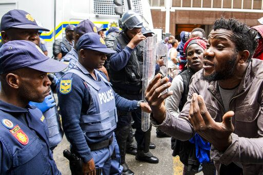FILE - In this Wednesday, Oct. 30, 2019 file photo police clash with protesters outside the U.N. refugee agency's offices in Cape Town, South Africa.  The Home Affairs Ministry says that, as of Jan. 1 2020, South Africa can strip refugees of their status if they engage in any political activity related to their home countries.
