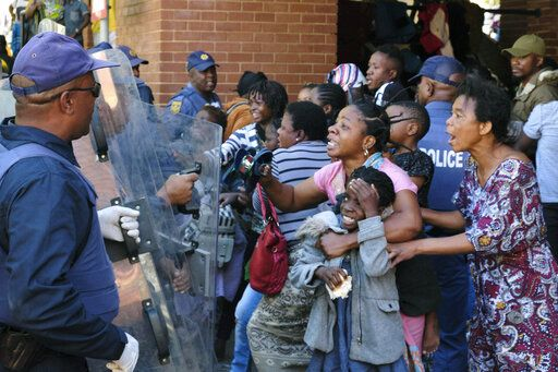 FILE - In this file photo taken Friday, Nov. 15, 2019 refugees, mostly from the Democratic Republic of Congo, face off with police, at the United Nations High Commissioner for Refugees (UNHCR) compound in Pretoria, South Africa.  The Home Affairs Ministry says that, as of Jan. 1 2020, South Africa can strip refugees of their status if they engage in any political activity related to their home countries.