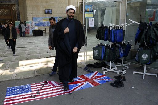 A cleric walks on the U.S. and British flags while leaving a gathering to commemorate the late Iranian Gen. Qassem Soleimani, who was killed in Iraq in a U.S. drone attack on Jan. 3, and victims of the Ukrainian plane that was mistakenly downed by the Revolutionary Guard last Wednesday, at the Tehran University campus in Tehran, Iran, Tuesday, Jan. 14, 2020. M