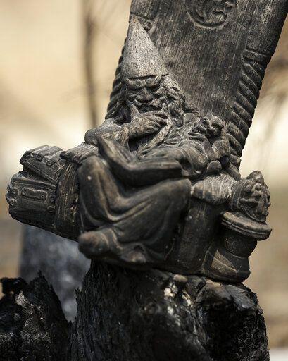 A blackened wizard ornament sits in a scorched fencepost at Nerrigundah, Australia, Monday, Jan. 13, 2020, after a wildfire ripped through the town on New Year's Eve. The tiny village of Nerrigundah in New South Wales has been among the hardest hit by Australia's devastating wildfires, with about two thirds of the homes destroyed and a 71-year-old man killed.