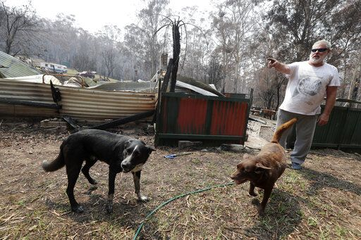 Lyle Stewart stands in front of his destroyed home at Nerrigundah, Australia, Monday, Jan. 13, 2020, after a wildfire ripped through the town on New Year's Eve. The tiny village of Nerrigundah in New South Wales has been among the hardest hit by Australia's devastating wildfires, with about two thirds of the homes destroyed and a 71-year-old man killed.