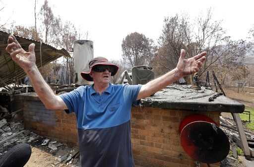 Colin Brennan stands in the debris of his destroyed house lost in the New Year's Eve wildfire at Nerrigundah, Australia, Monday, Jan. 13, 2020. The tiny village of Nerrigundah in New South Wales has been among the hardest hit by Australia's devastating wildfires, with about two thirds of the homes destroyed and a 71-year-old man killed.
