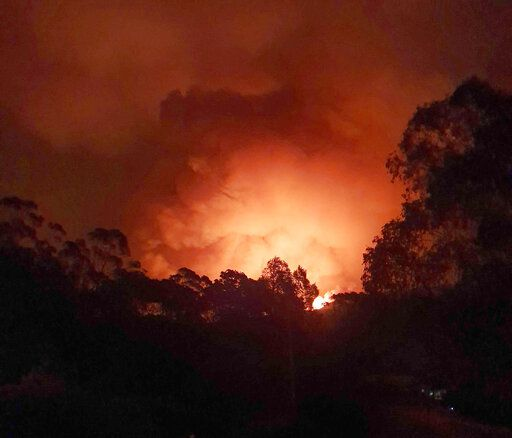 In this Dec. 31, 2019, photo provided by Siobhan Threlfall, a fire approaches the village of Nerrigundah, Australia. The tiny village has been among the hardest hit by Australia's devastating wildfires, with about two thirds of the homes destroyed and a 71-year-old man killed.