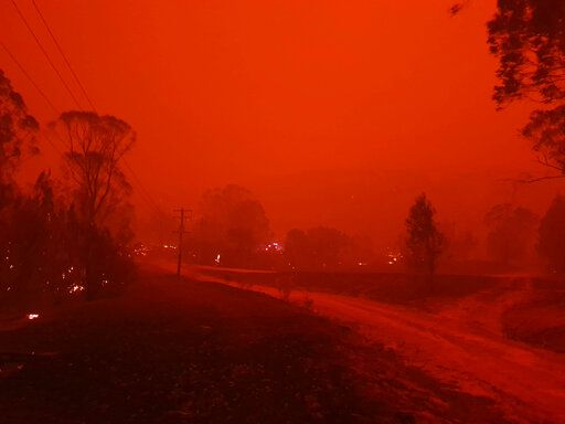 In this Dec. 31, 2019, photo provided by Siobhan Threlfall, fire and thick smoke remains the village of Nerrigundah, Australia. The tiny village has been among the hardest hit by Australia's devastating wildfires, with about two thirds of the homes destroyed and a 71-year-old man killed.