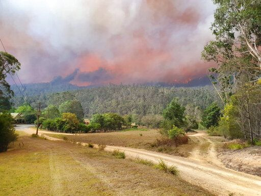 In this Dec. 30, 2019, photo provided by Siobhan Threlfall, a fire approaches the village of Nerrigundah, Australia. The tiny village has been among the hardest hit by Australia's devastating wildfires, about with two thirds of the homes destroyed and a 71-year-old man killed.