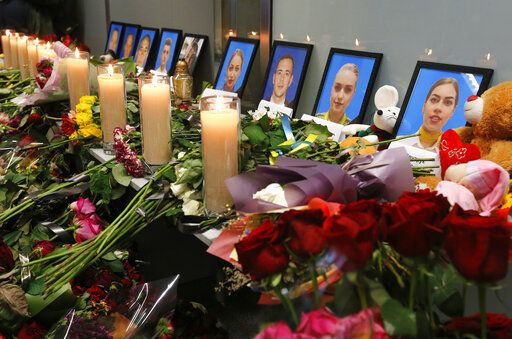 Flowers and candles are placed in front of portraits of the flight crew members of the Ukrainian 737-800 plane that crashed on the outskirts of Tehran, at a memorial inside Borispil international airport outside Kyiv, Ukraine, Saturday, Jan. 11, 2020. Ukraine's President Volodymyr Zelenskiy says that Iran must take further steps following its admission that one of its missiles shot down Ukrainian civilian airliner. He also expressed hope for the continuation of the crash investigation without delay. A team of Ukrainian investigators is in Iran.