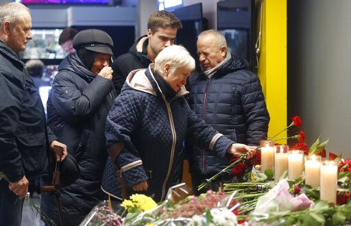 Relatives of one of the flight crew members of the Ukrainian 737-800 plane that crashed on the outskirts of Tehran, stand at a memorial inside Borispil international airport outside Kyiv, Ukraine, Saturday, Jan. 11, 2020. Ukraine's President Volodymyr Zelenskiy says that Iran must take further steps following its admission that one of its missiles shot down Ukrainian civilian airliner.