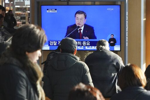 People watch a TV screen showing the live broadcast of South Korean President Moon Jae-in's New Year's press conference at the Seoul Railway Station in Seoul, South Korea, Tuesday, Jan. 14, 2020.