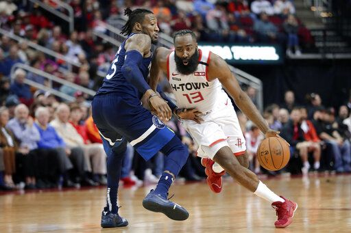 Houston Rockets guard James Harden (13) drives around Minnesota Timberwolves forward Robert Covington, left, during the second half of an NBA basketball game Saturday, Jan. 11, 2020, in Houston.