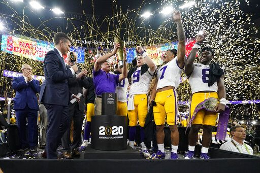 LSU head coach Ed Orgeron holds the trophy after their win against Clemson in a NCAA College Football Playoff national championship game Monday, Jan. 13, 2020, in New Orleans. LSU won 42-25.