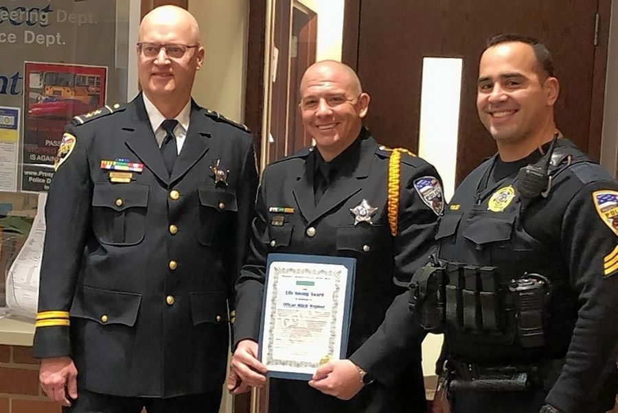 Prospect Heights police Officer Mitch Webber, center, is flanked by Deputy Chief Mark Porlier, left, and Sgt. Mark Pufundt, right, as he receives the city's Life Saving Award at Monday's city council meeting for helping rescue a man in cardiac arrest last month.