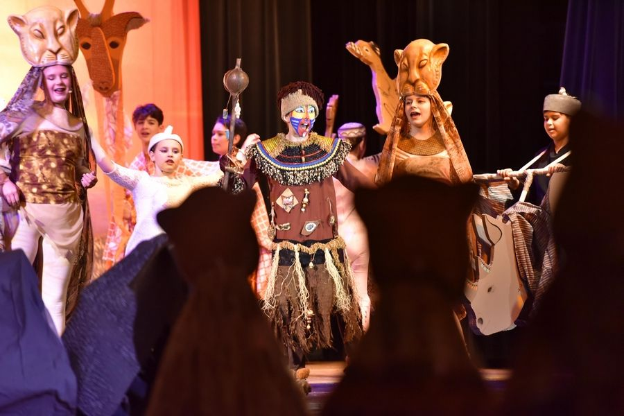"Rafiki, played by Carl Sandburg Middle School seventh-grader Chloe Langford, leads the opening act as the 44 other members of the cast dance on stage and through the audience during a dress rehearsal for ""The Lion King Jr."" on Wednesday at Lincoln Early Learning Center in Mundelein."