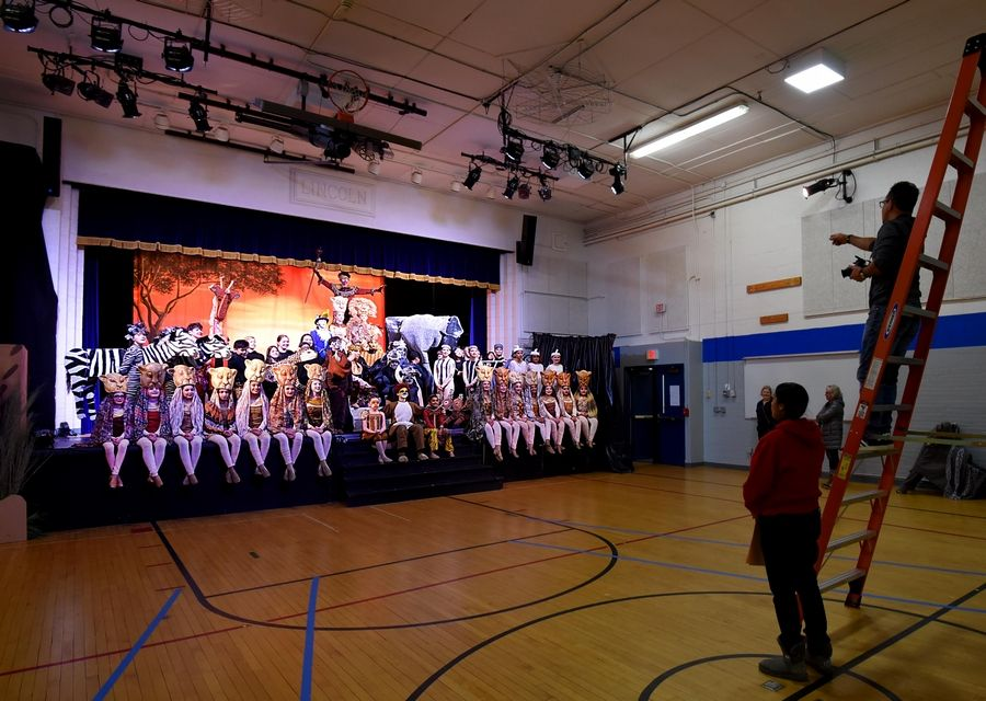 "The 45 cast members and 25 crew pose on stage for a photo Wednesday before the Carl Sandburg Middle School dress rehearsal of ""The Lion King Jr."" at the Lincoln Early Learning Center in Mundelein."