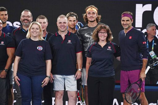 Roger Federer of Switzerland, second right, and Stefanos Tsitsipas of Greece, fourth right, pose with Deb Borg, third right, and fellow Australian firefighters during the Rally For Relief at Rod Laver Arena in Melbourne, Wednesday, Jan. 15, 2020. Tennis stars have come together for the Rally for Relief to raise money in aid of the bushfire relief efforts across Australia. (Scott Barbour/AAP Image via AP)