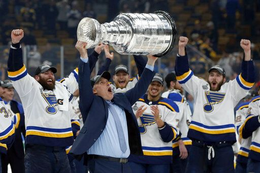FILE- In this June 12, 2019, file photo, St. Louis Blues coach Craig Berube carries the Stanley Cup after the Blues defeated the Boston Bruins in Game 7 of the NHL Stanley Cup Final in Boston. Berube took over as coach of the St. Louis Blues in November 2018 and led them from dead last in the standings in January to their first Stanley Cup title.