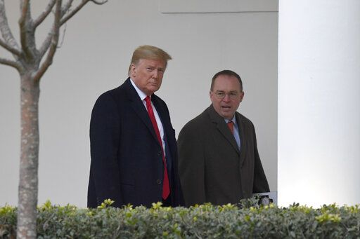 FILE - In this Jan. 13, 2020. file photo, President Donald Trump, left, and acting White House chief of staff Mick Mulvaney, right, walk along the colonnade of the White House in Washington. The federal government's watchdog agency says a White House office violated federal law in withholding security assistance to Ukraine aid. The Government Accountability Office said Thursday the White House Office of Management and Budget violated the law in holding up the assistance.